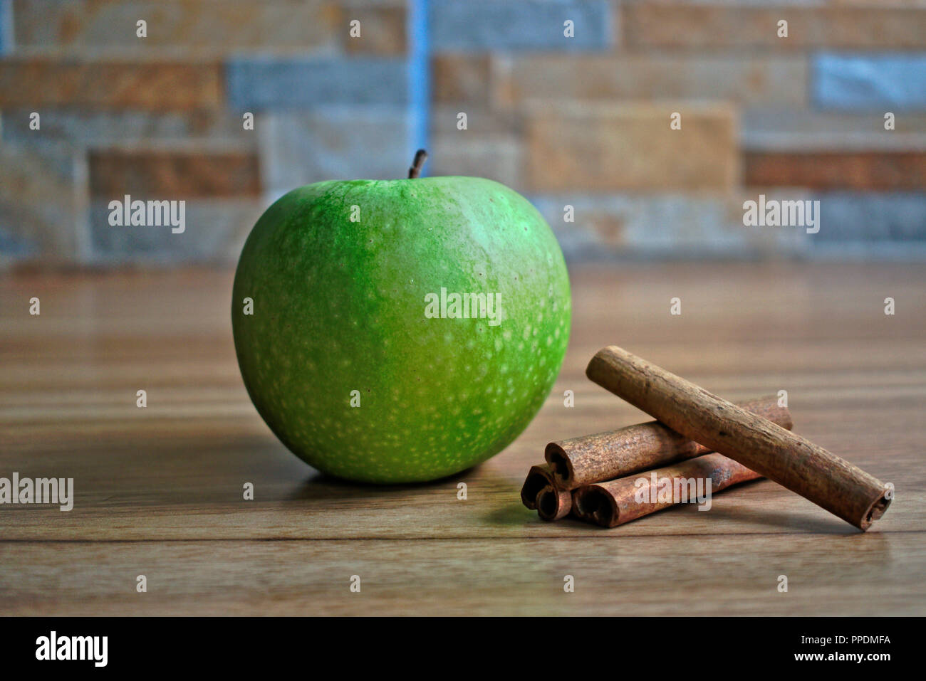 Green apple and cinnamon sticks on a wooden table - Stock Image