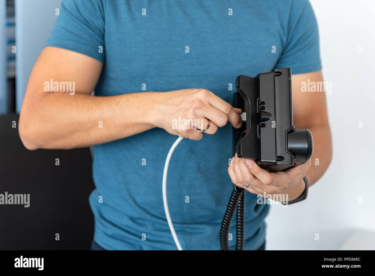 VoIP Telephony, technical support, services. Specialist connects the phone to the network Stock Photo