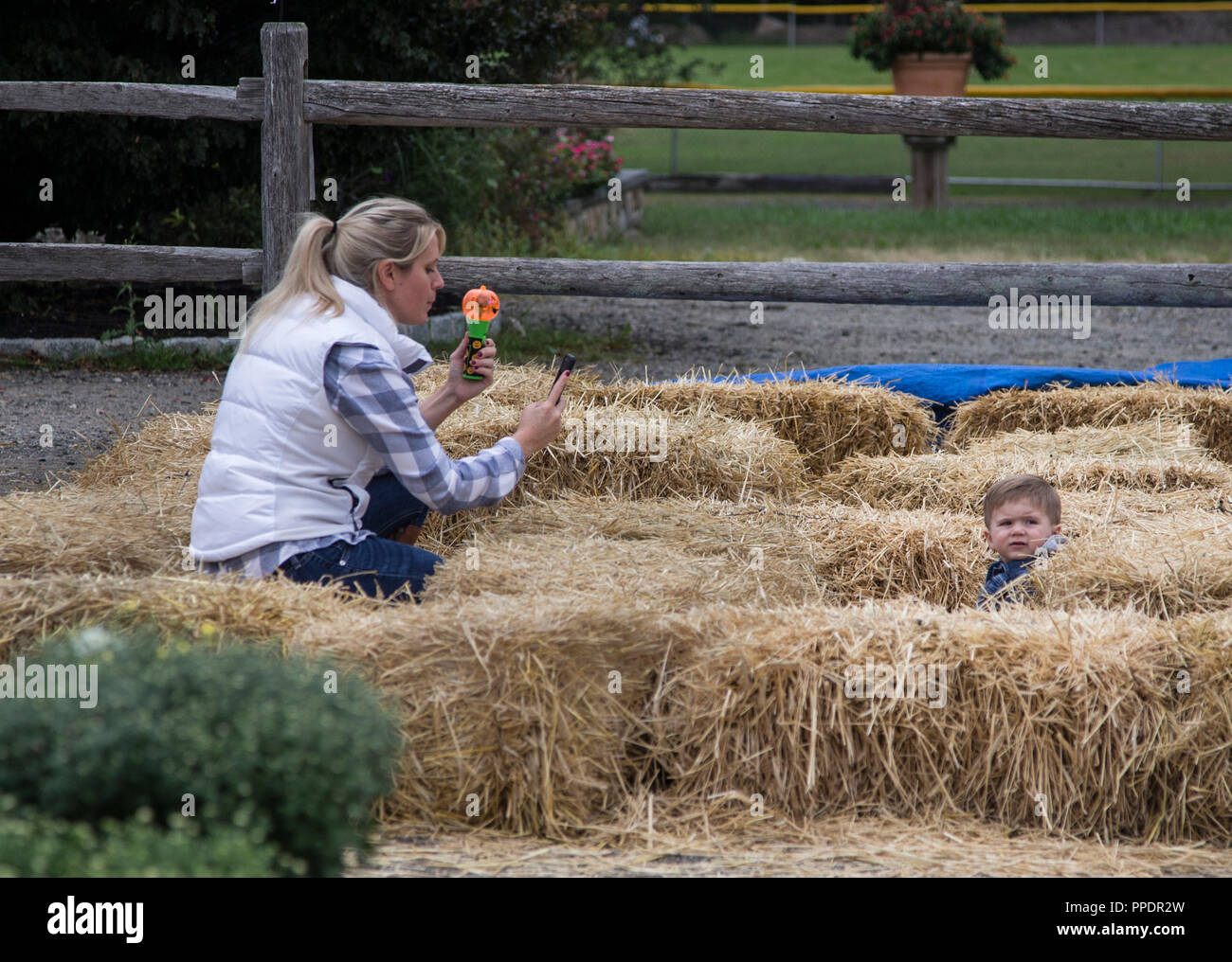 Mother taking a cellphone picture of her son surrounded by bales of hay - Stock Image