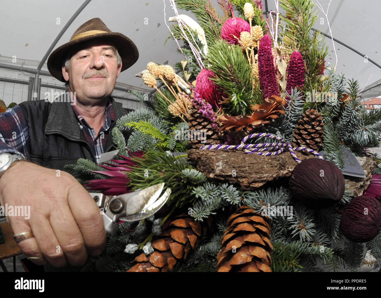 "Johann Raab from the family business ""Blumen und Grabpflege Franziska Raab"" from Perlach makes a floral arrangement as grave decoration for All Saints' Day. Stock Photo"