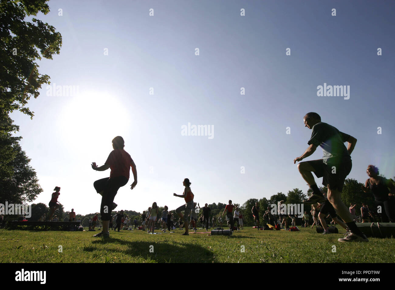 Recreational athletes move under the guidance of a trainer at the 'Gym in the Park', a fitness program of the City of Munich, which is held daily at 18.00 clock in specific parks in Munich. - Stock Image