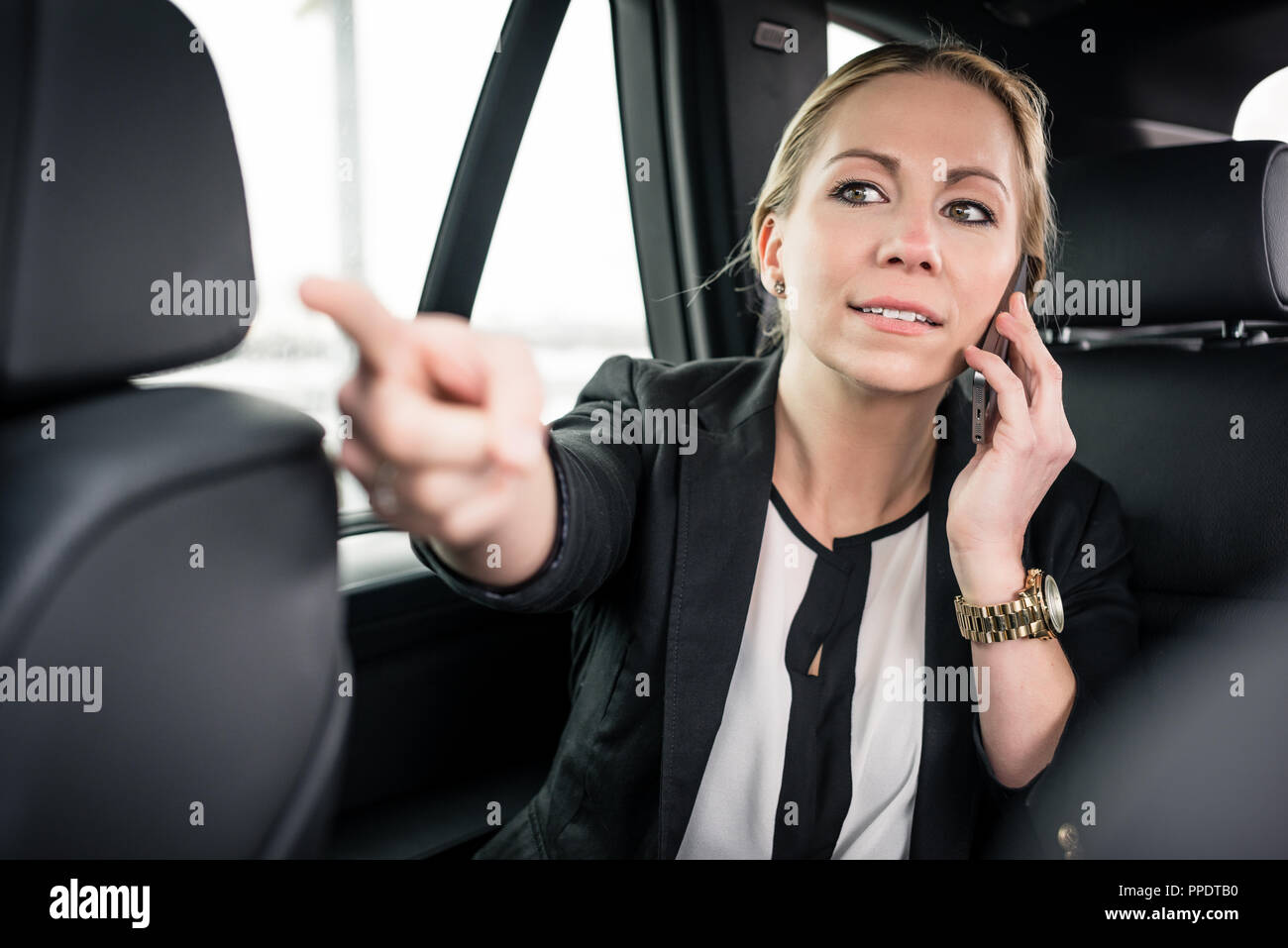 Businesswoman on call pointing finger in car  - Stock Image