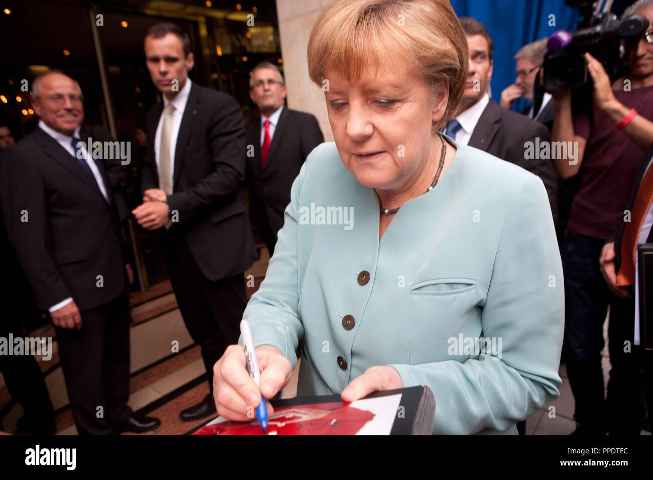 Angela Merkel gives autographs on her arrival at Bayerischer Hof. - Stock Image