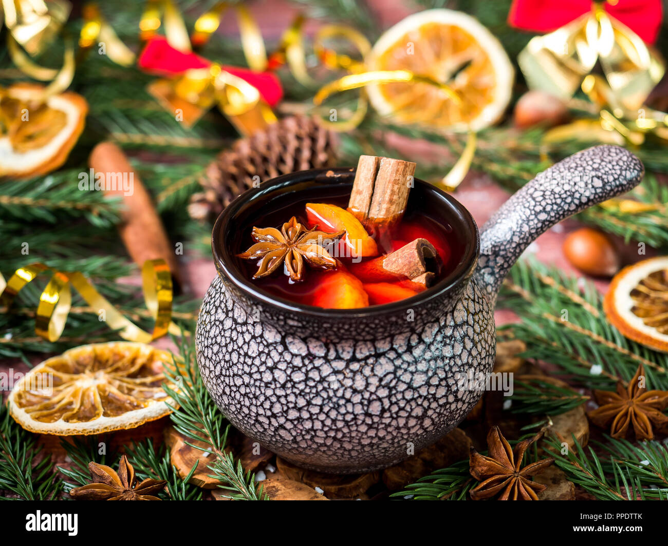 Christmas mulled wine with cinnamon, orange and star anise in a ceramic bowl with winter decorations. - Stock Image