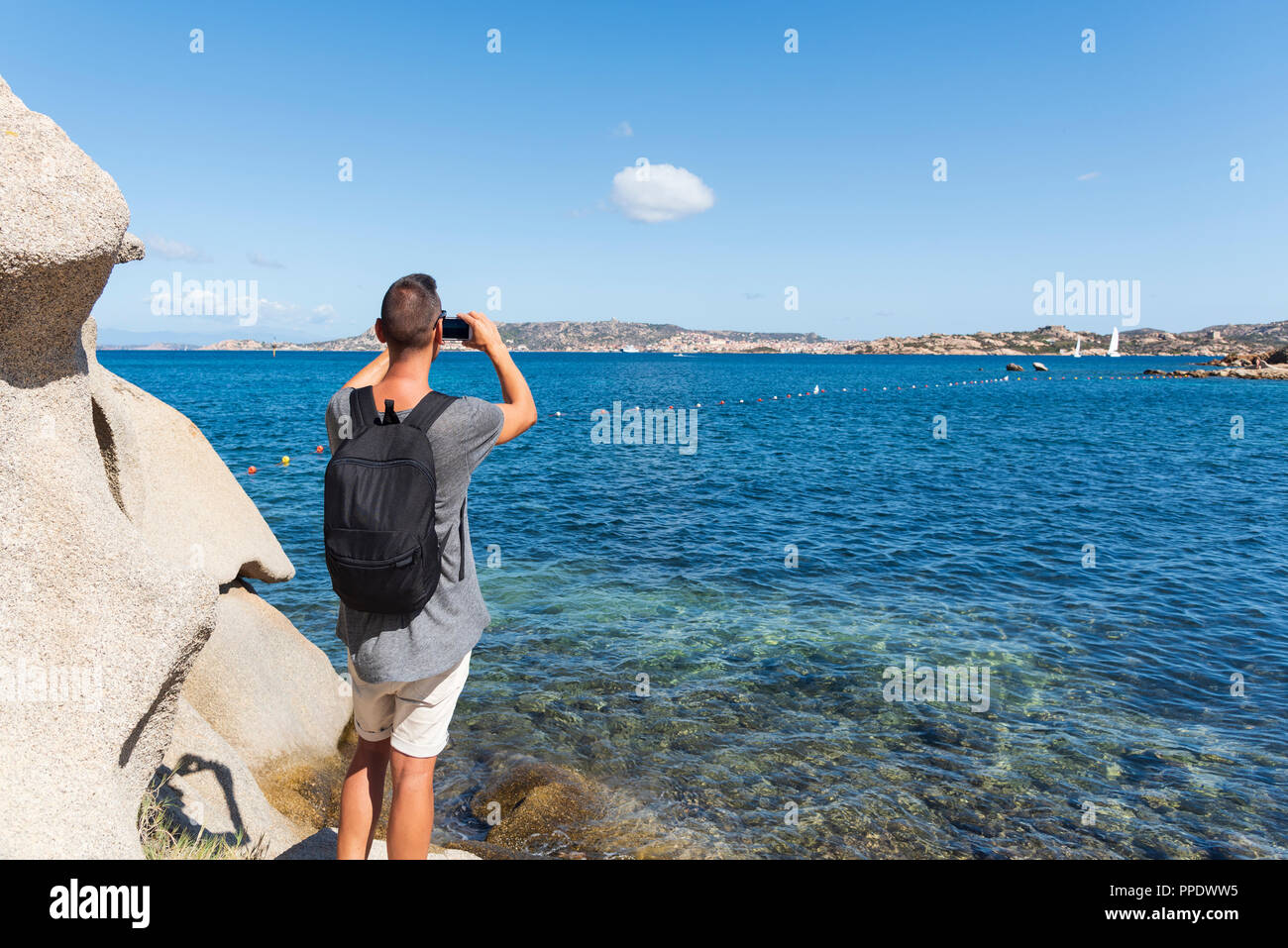young caucasian man taking a photo of the coast of the Mediterranean sea in Sardinia, Italy, highlighting La Maddalena, Santo Stefano and Caprera isla - Stock Image