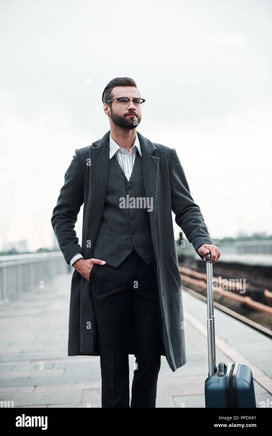 Business trip. Young businessman walking near railway with luggage confident - Stock Image