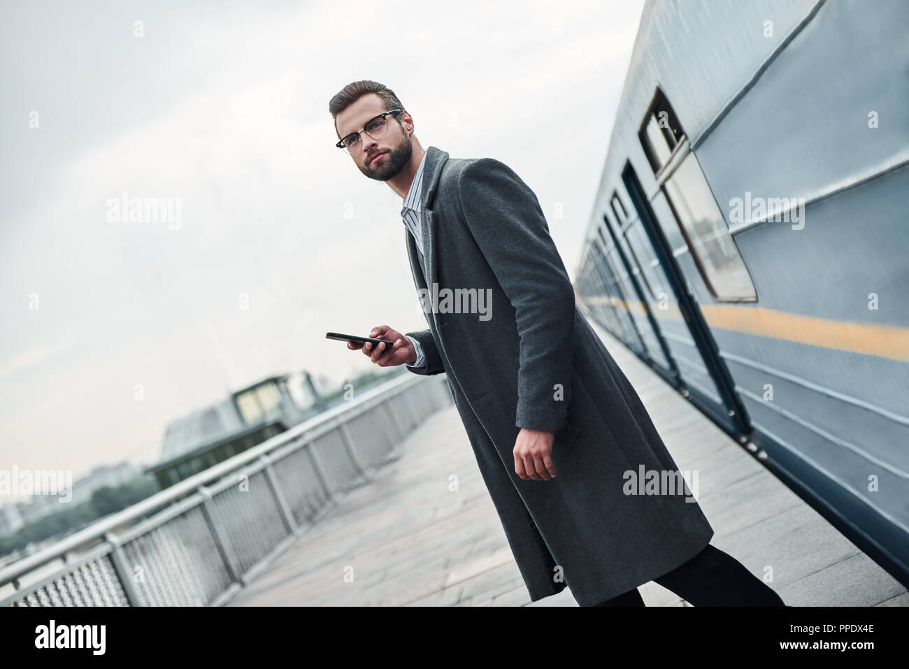 Business trip. Young businessman standing near railway holding smartphone looking aside pensive - Stock Image