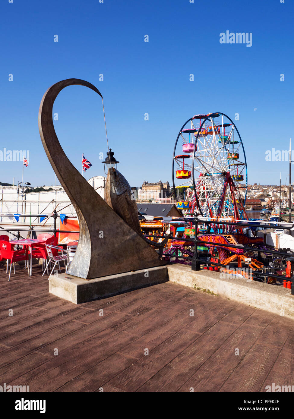 Tunny Fish sculpture by Ray Lonsdale on the East Pier with the Luna Park ferris wheel beyond Scarborough Yorkshire England - Stock Image