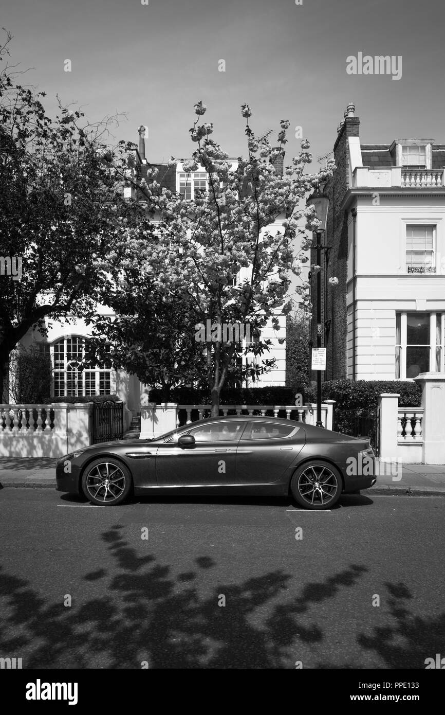 Aston Martin parked in front of expensive houses with trees in blossom. - Stock Image