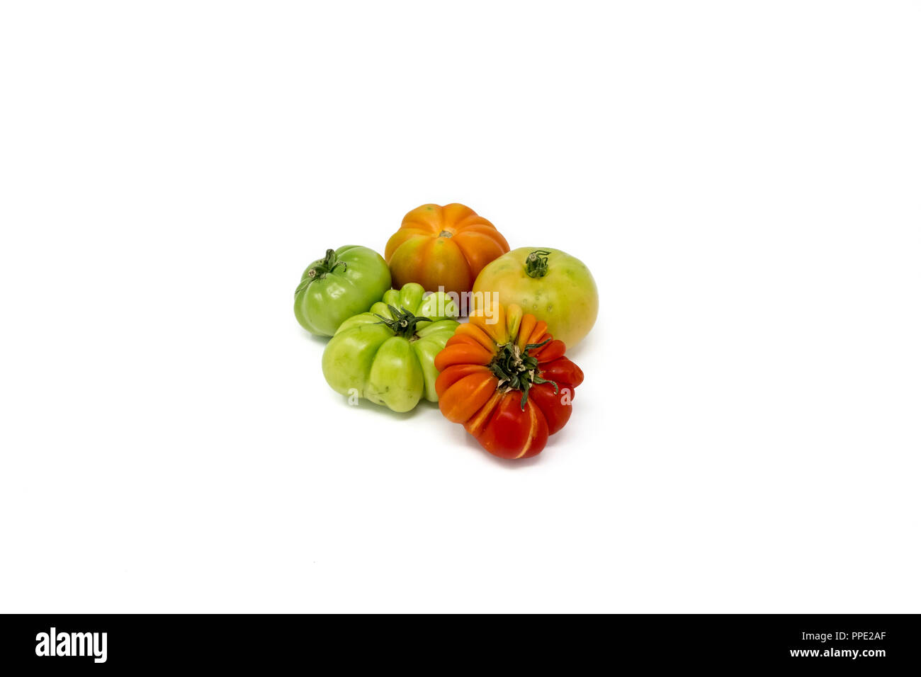 A variety of imperfect, ripening heirloom or heritage tomatoes in a studio setting - Stock Image