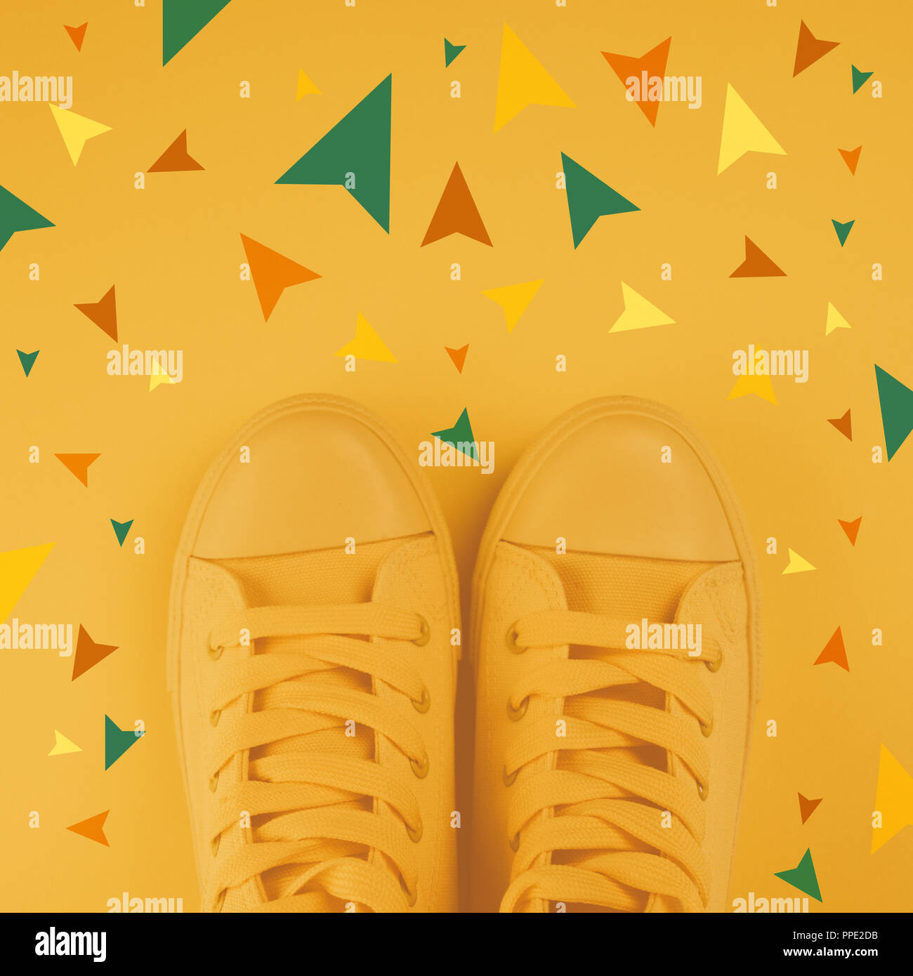 Making decisions and right choices in life concept, youth style sneakers from above with arrows pointing to different directions as if person had vari - Stock Image