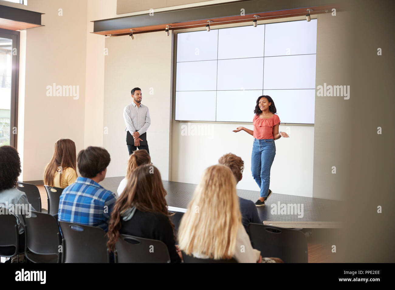 Female Student Giving Presentation To High School Class In Front Of Screen Stock Photo