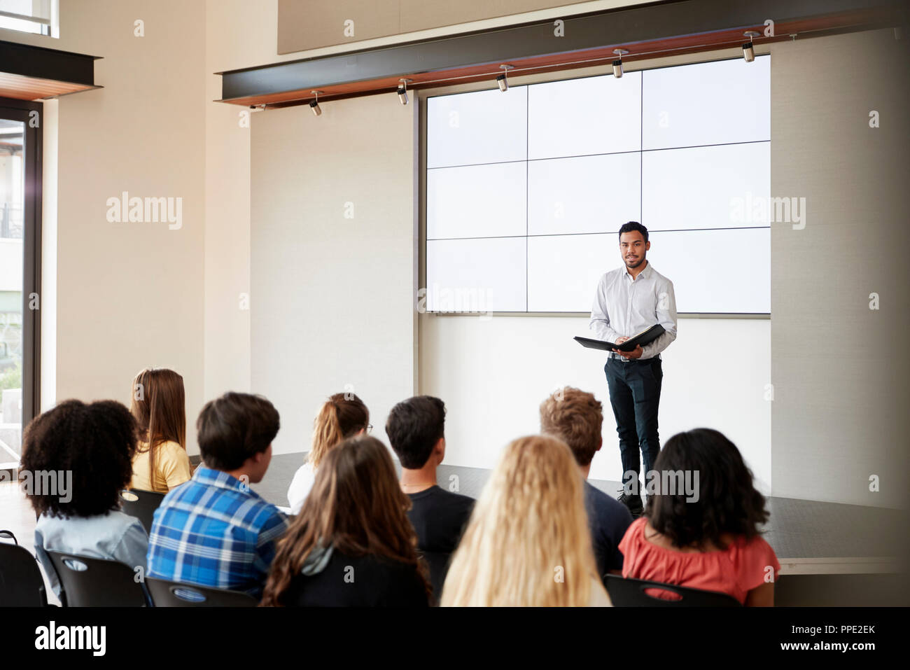 Teacher Giving Presentation To High School Class In Front Of Screen Stock Photo