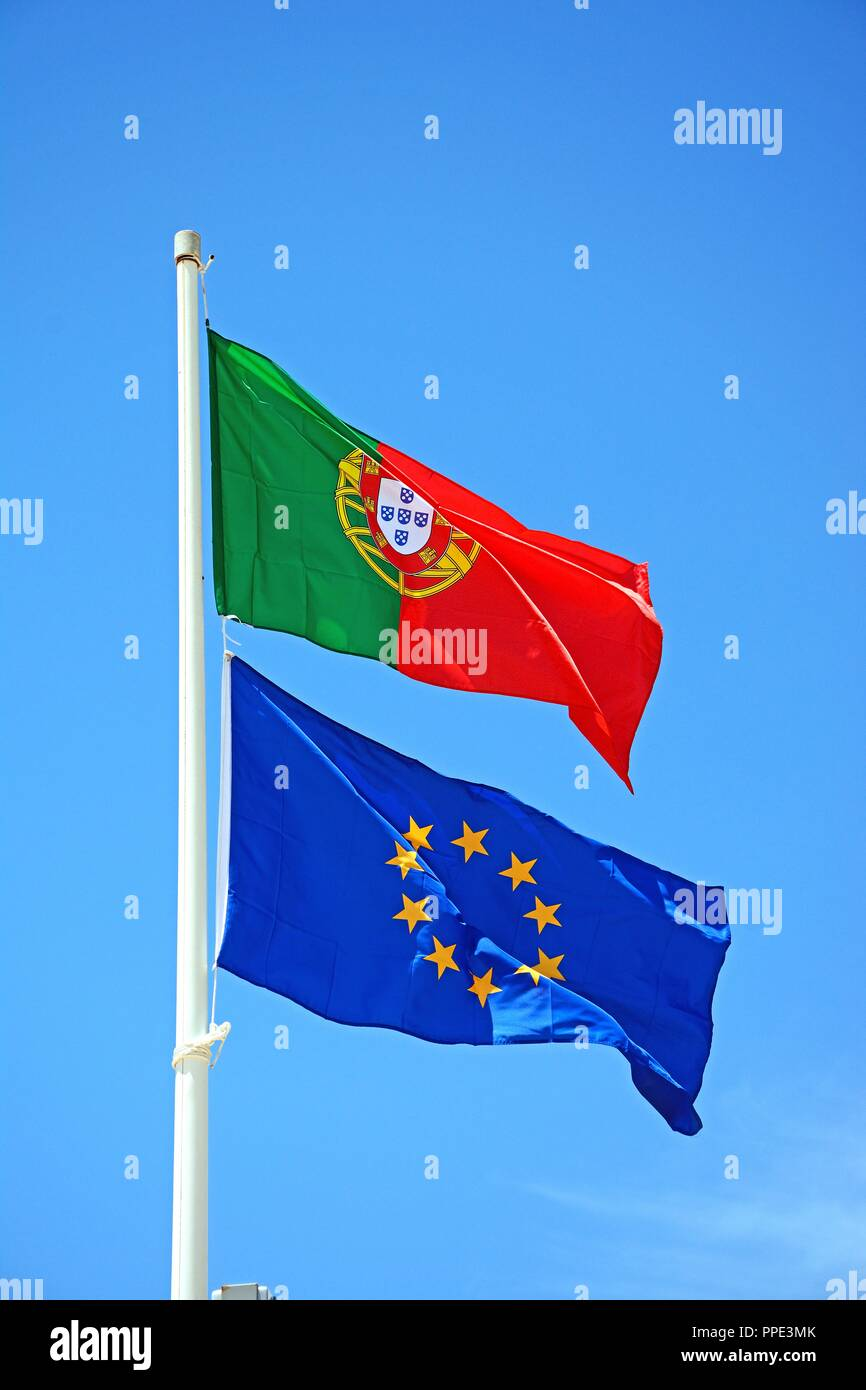Portuguese and European Union Flags flapping against a blue sky, Praia da Monte Gordo; Vila Real de Santo Antonio, Algarve, Portugal, Europe. - Stock Image