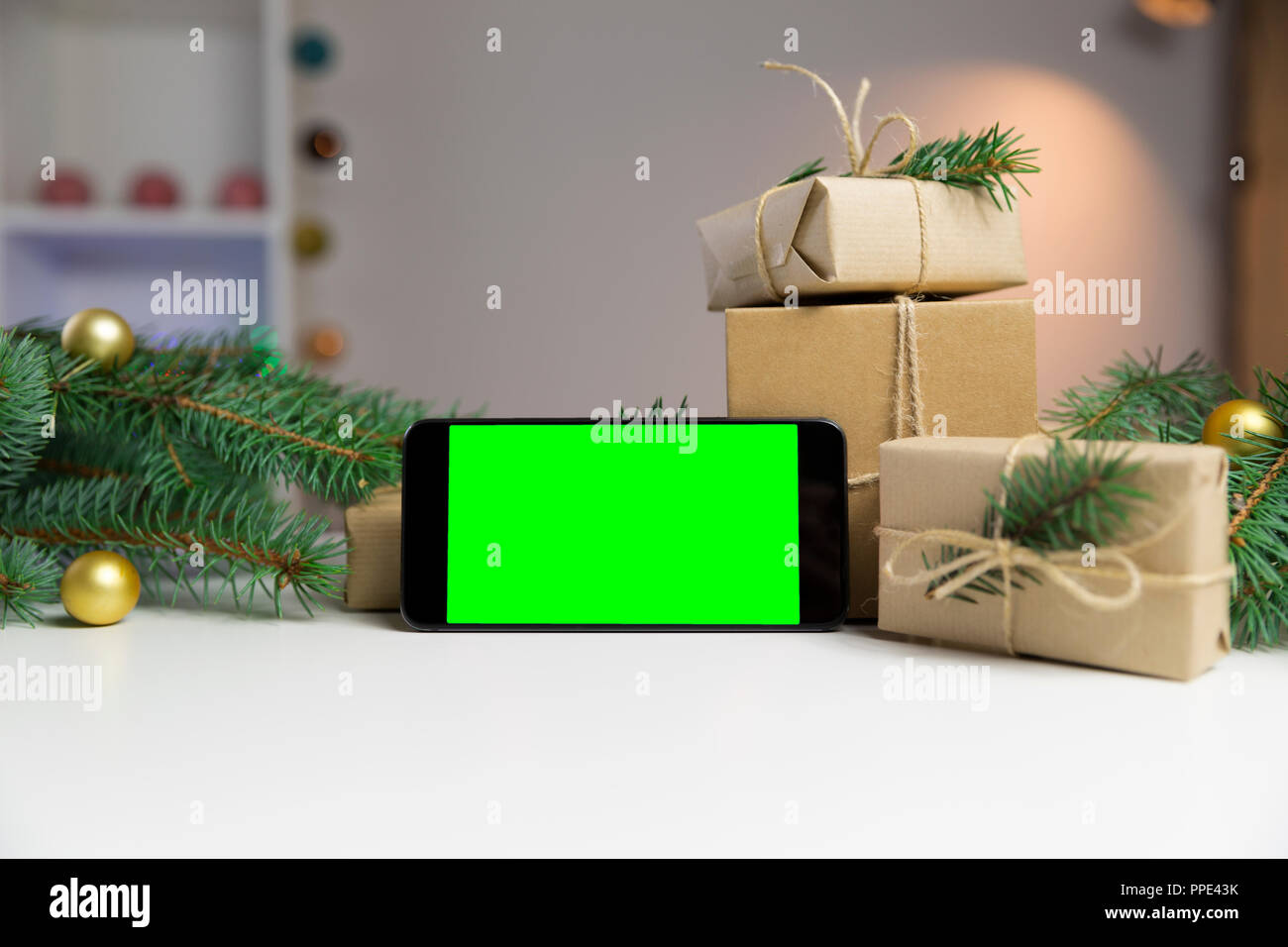 Smart phone with green screen surrounded by Christmas decorations ...