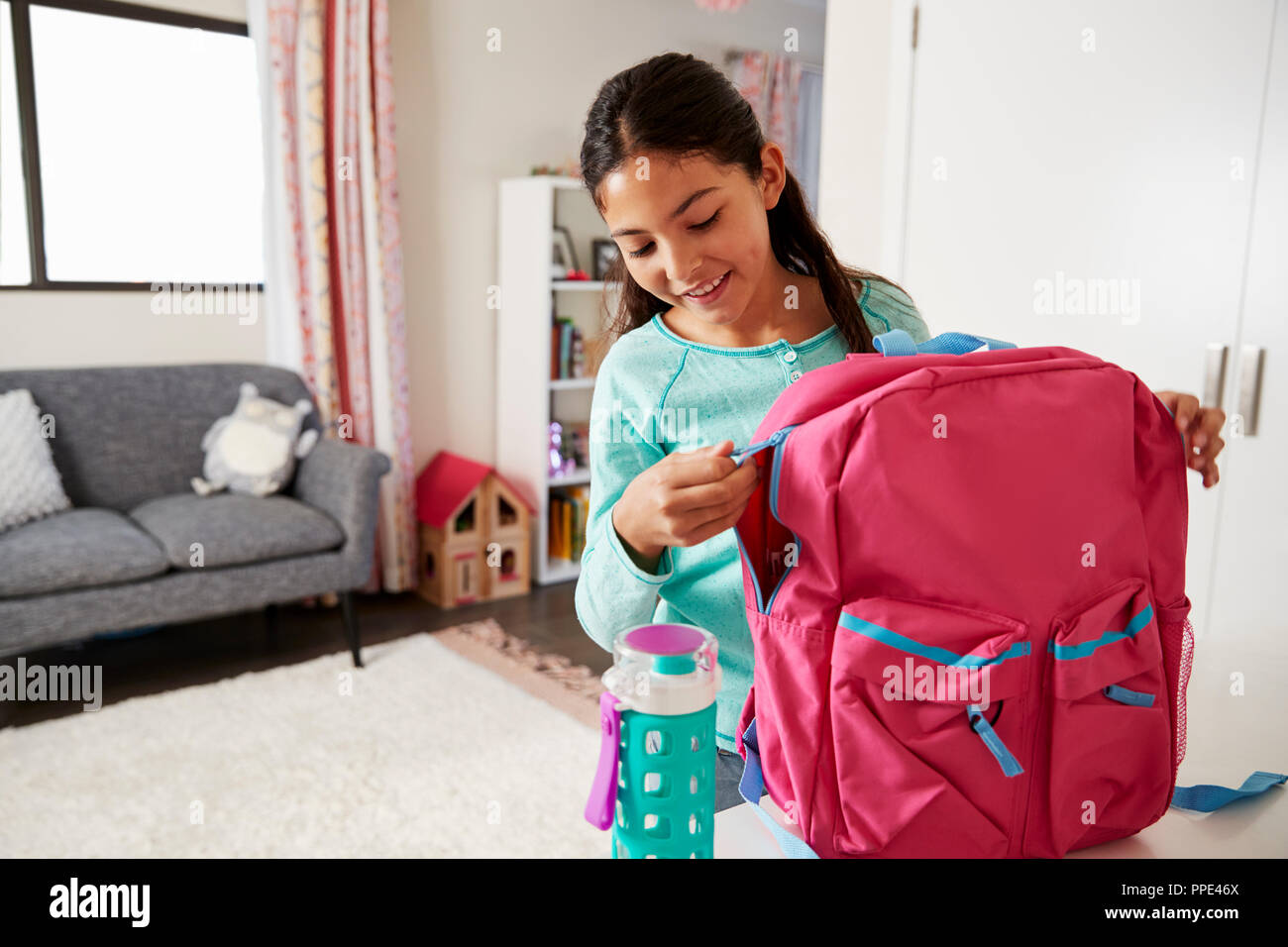 Young Girl In Bedroom Zipping Up Bag Ready For School - Stock Image