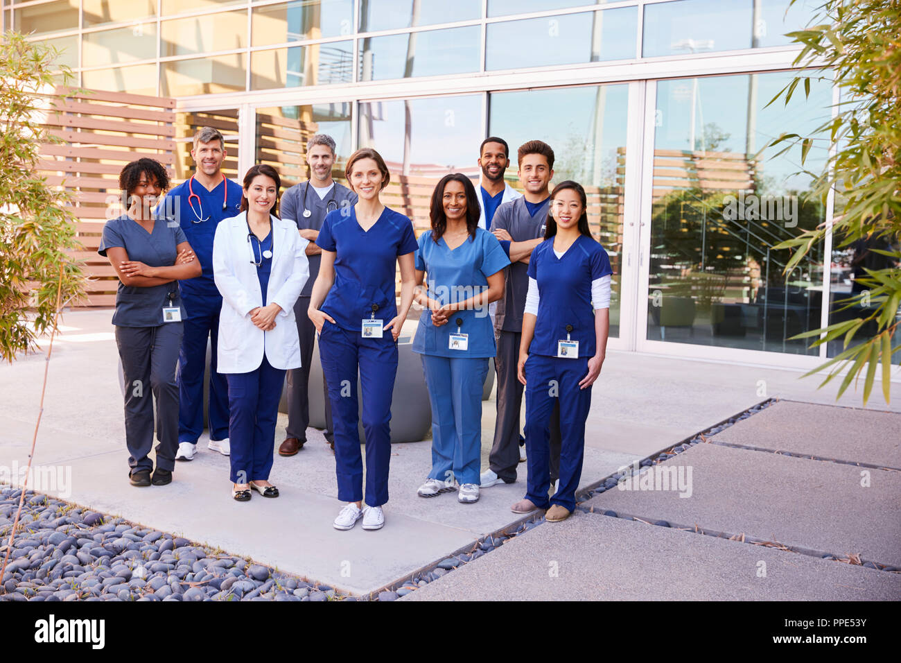 healthcare team with id badges stand outdoors full length stock