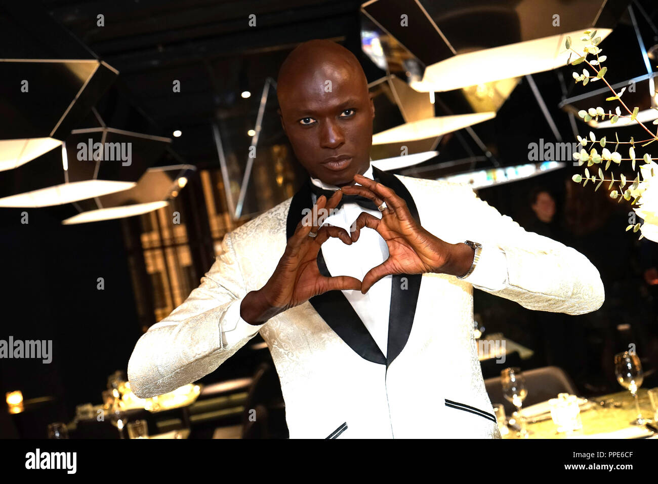 Model Papis Loveday forms the logo of the house with his hands at the opening of the first private member' club of Munich in the Old Stock Exchange building at Lenbachplatz. - Stock Image