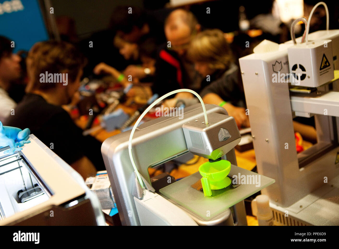 3-D printer at the Elektro Conrad stand at the maker fair 'Make Munich' in the Tonhalle of the Kultfabrik. It heats plastic and prints it in many layers on top of each other. Here is a green cup. - Stock Image