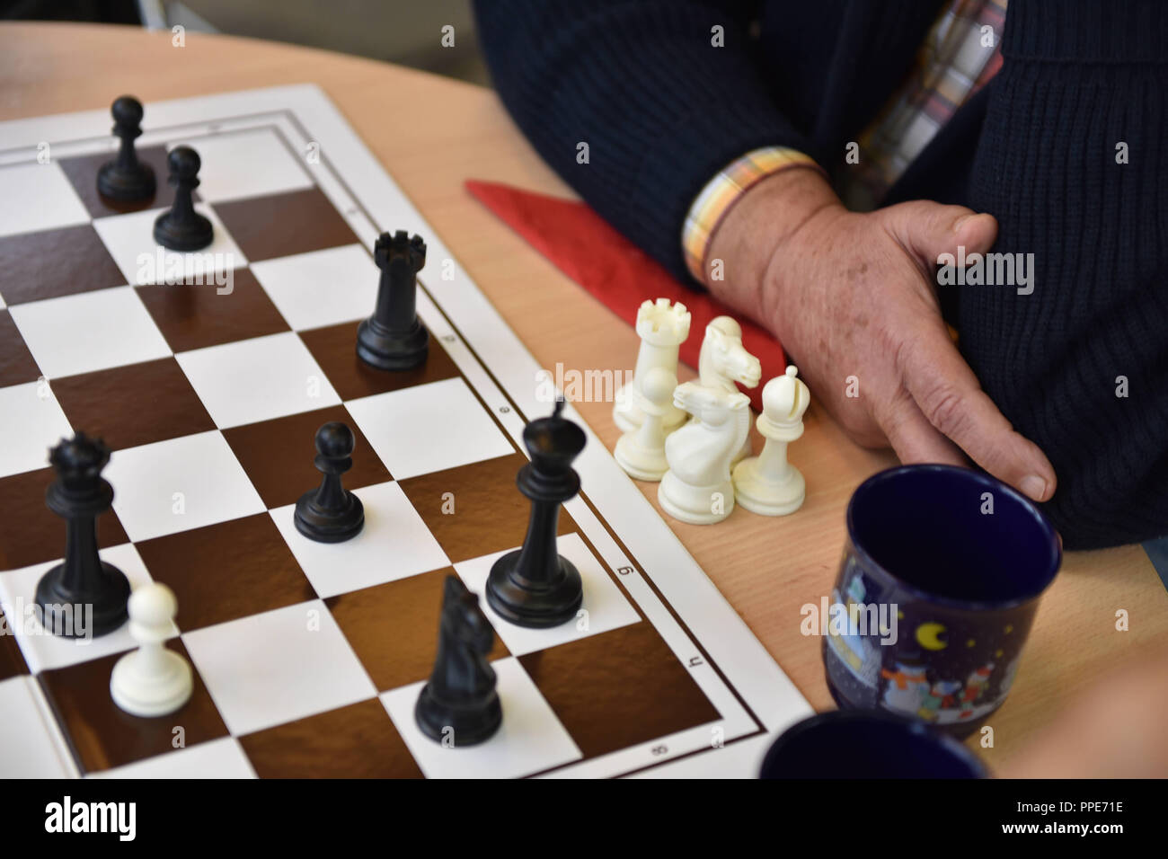 Older people playing chess together in the community center of the sheltered accommodation of Diakonie Hasenbergl on Schleissheimer Strasse. In particular poor and lonely seniors are to be integrated again into a life worth living. - Stock Image
