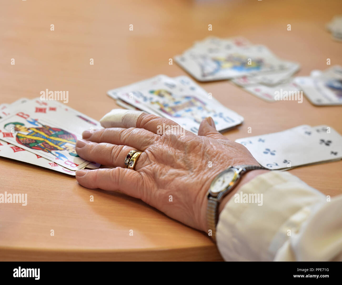 Older people playing a card game together in the community center of the sheltered accommodation of Diakonie Hasenbergl on Schleissheimer Strasse. In particular poor and lonely seniors are to be integrated again into a life worth living. - Stock Image
