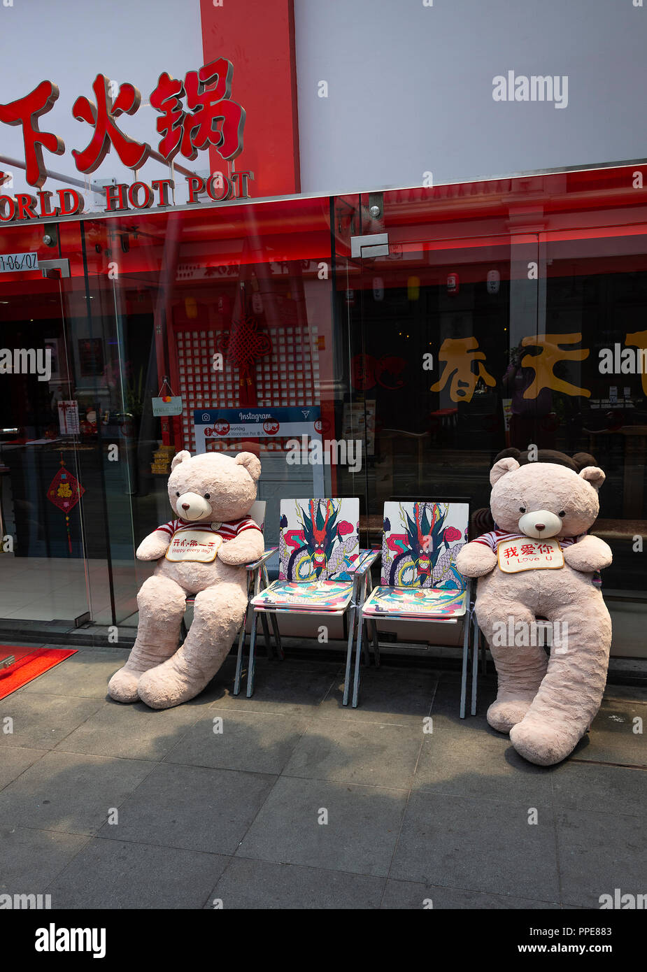Two Lovely Large Teady Bears Sitting on Colourful Chairs Outside Spice World Hot Spot Sichuan Restaurant in Clarke Quay Singapore Asia - Stock Image