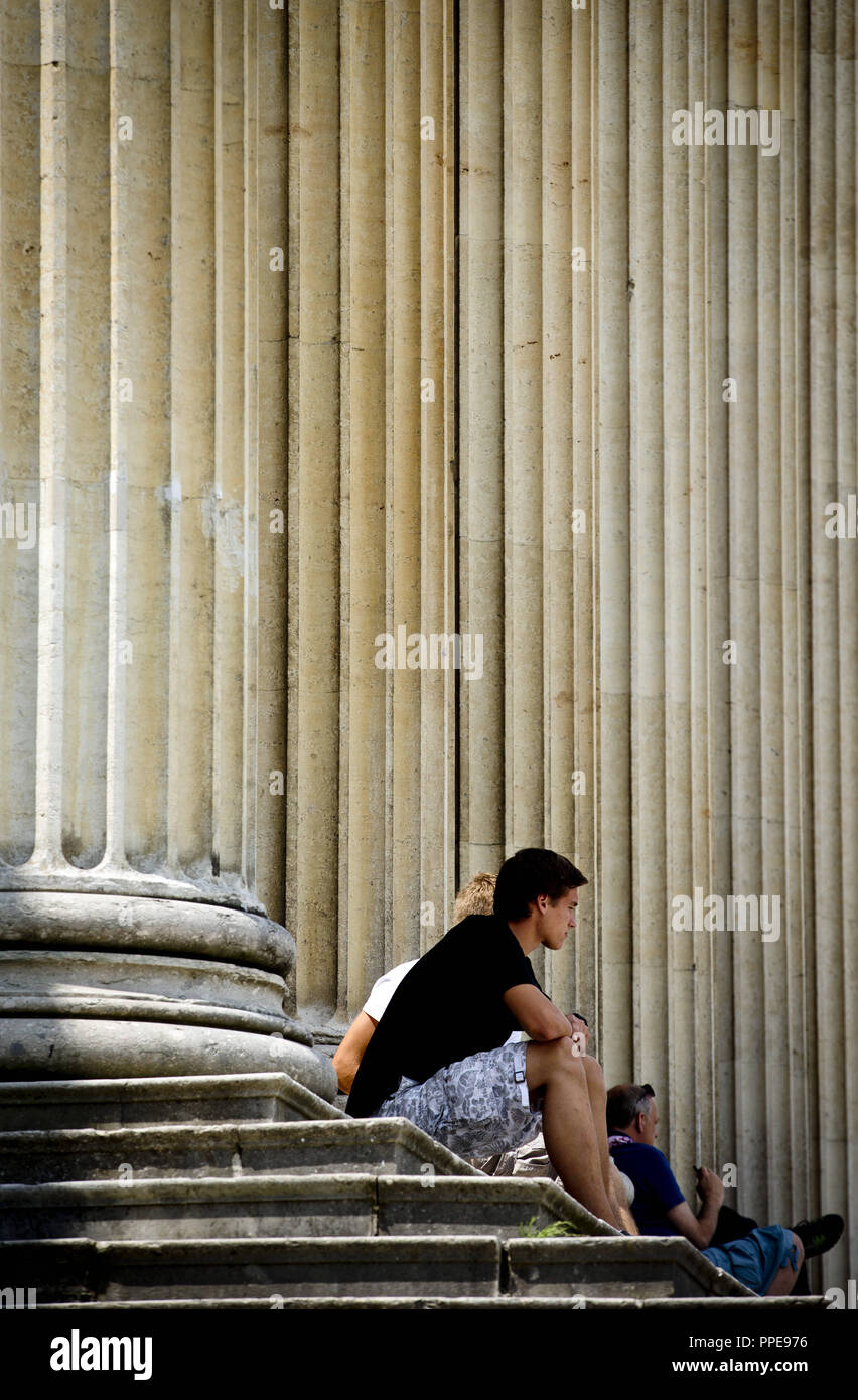 People sitting on the steps between the columns of the Staatliche Antikensammlungen (State Collections of Antiques) on Koenigsplatz in Munich. - Stock Image