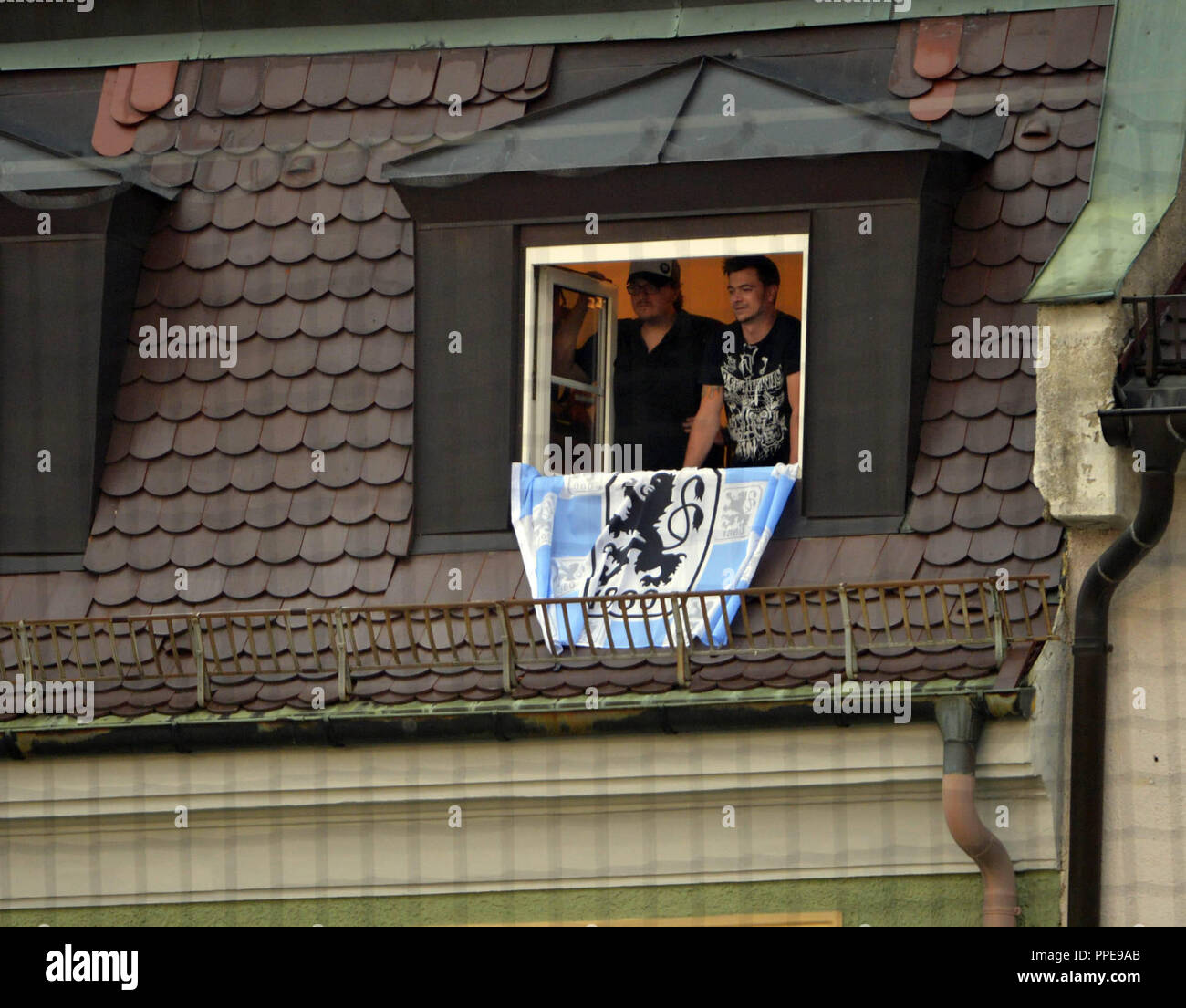 Two residents with Lion flag follow the Regionalliga Sued derby from their window: FC Bayern Munich II - TSV 1860 Muenchen (2-0) at the Municipal Stadium in the Gruenwalder Strasse in Munich. - Stock Image