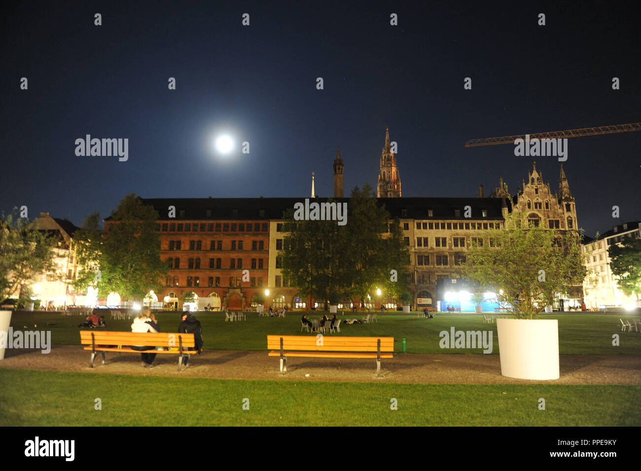 Moon rising above the green area at the Marienhof in Munich, with the Town Hall in the background. - Stock Image
