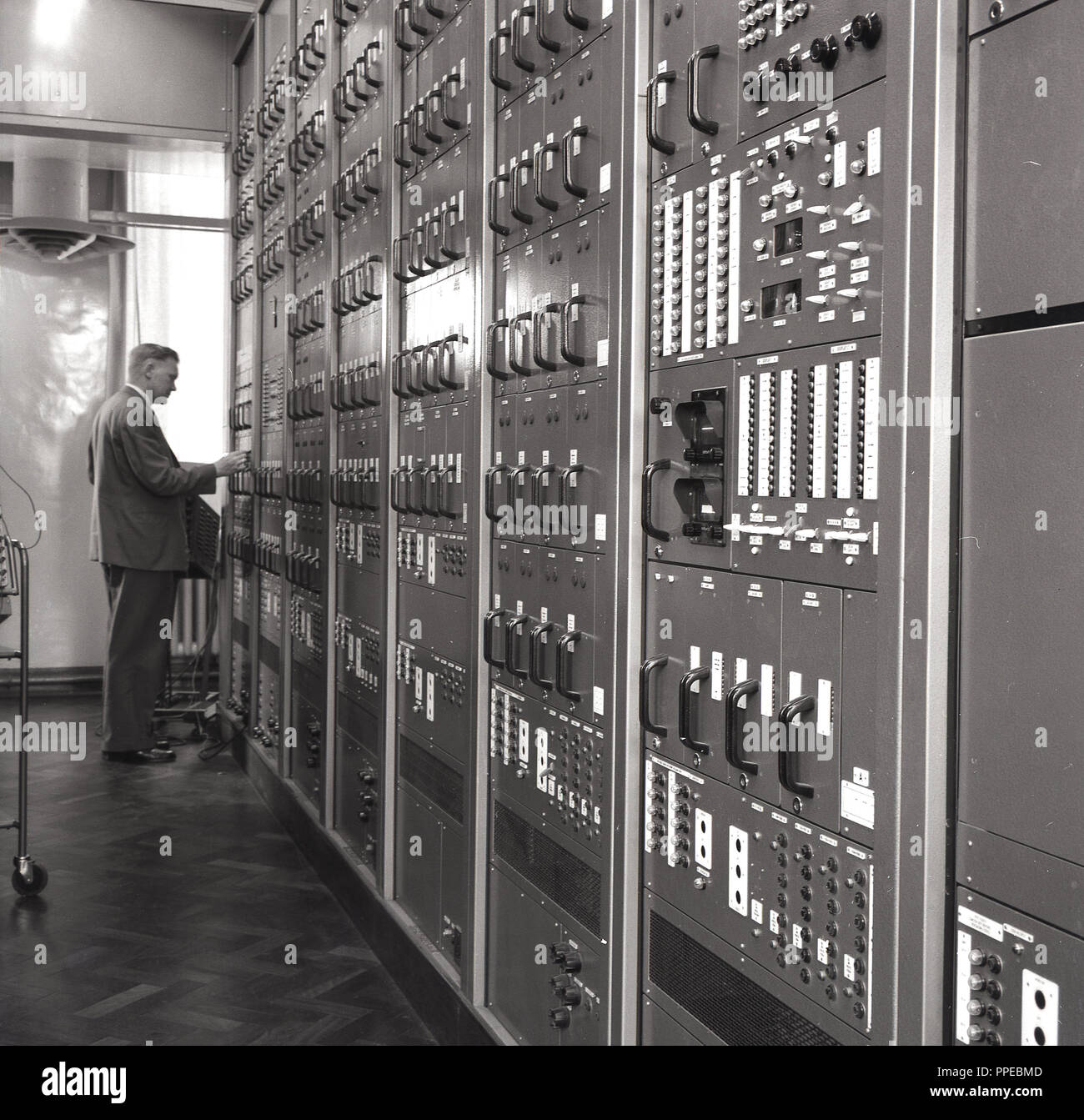 1950s, man checking on the operation of wireless broadcasting equipment or monitors, England, UK. - Stock Image