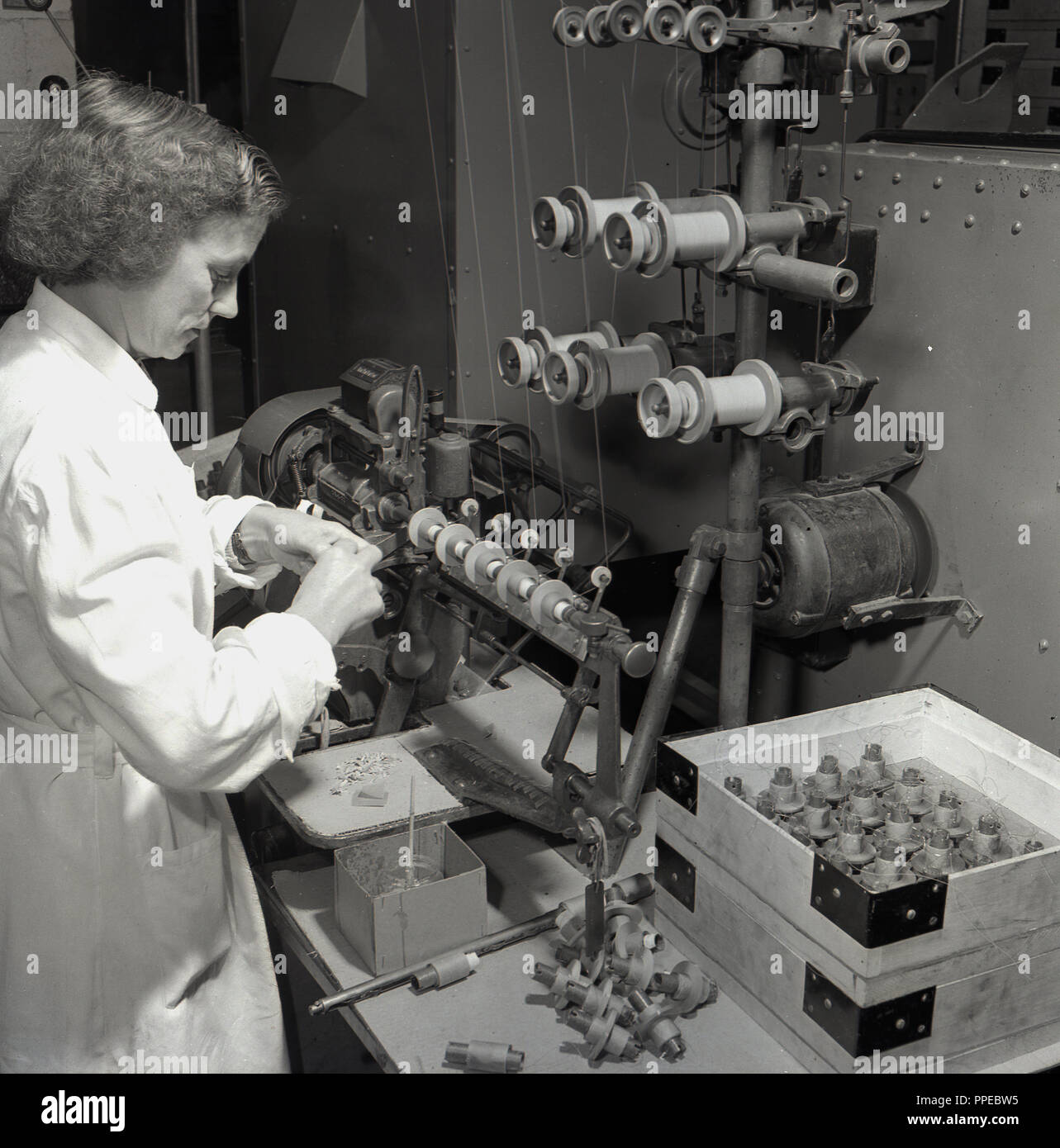 1950s, female worker checking parts for Bush Radio, a leading British electronics manufacturer of radios and TV sets in this era. - Stock Image