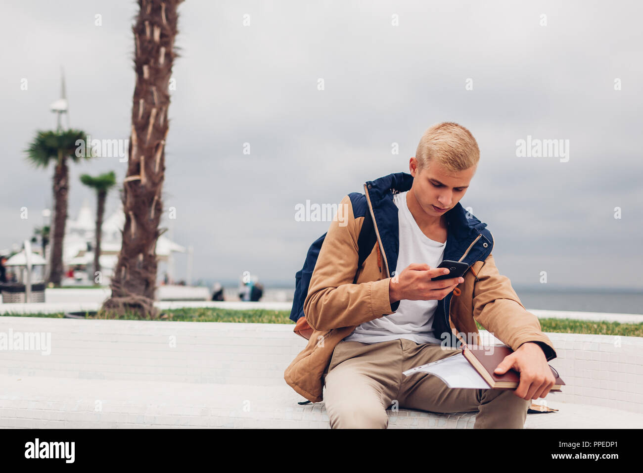 College student sitting on bench by sea using smartphone and holding book on Langeron beach in Odessa. Young man with backpack networking - Stock Image