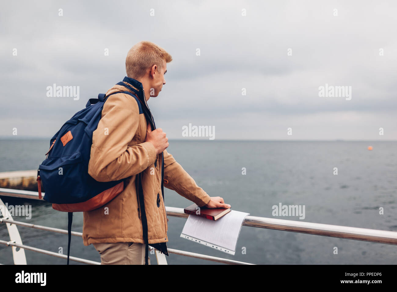 College student with backpack and book walking by sea after classes and admiring view on beach in Odessa. Young man thinking - Stock Image