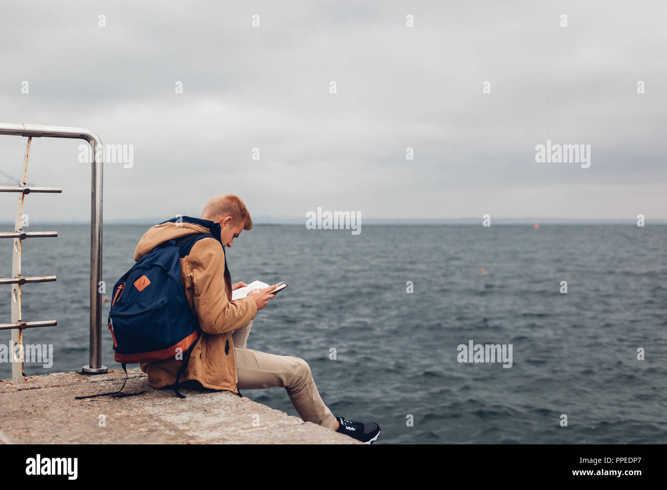 College student with backpack reading book by sea on pier in Odessa on rainy autumn day. Guy studying outdoors Stock Photo
