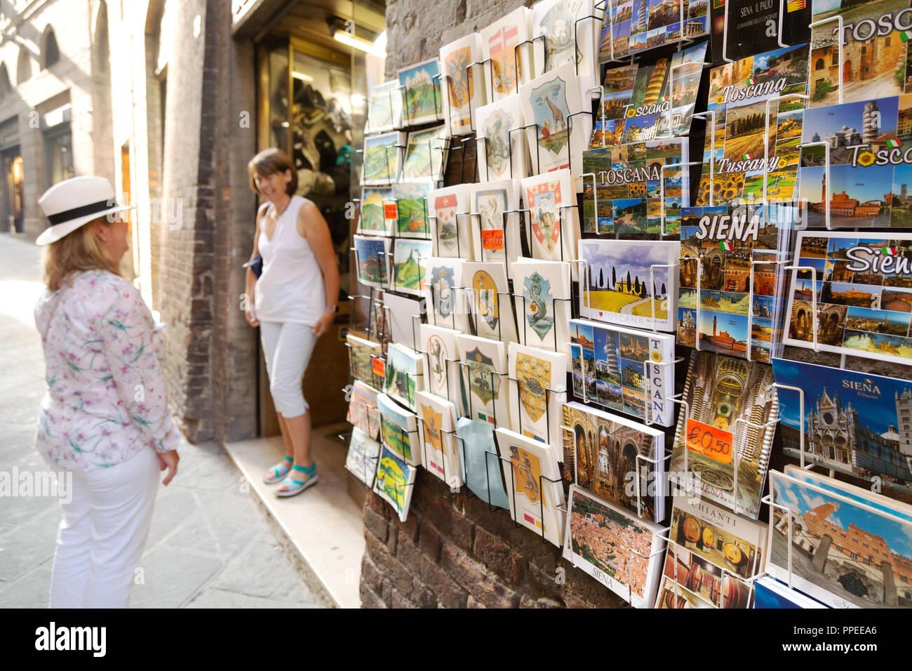 Tourists buying postcards on holiday, Siena, Tuscany, Italy Europe - Stock Image