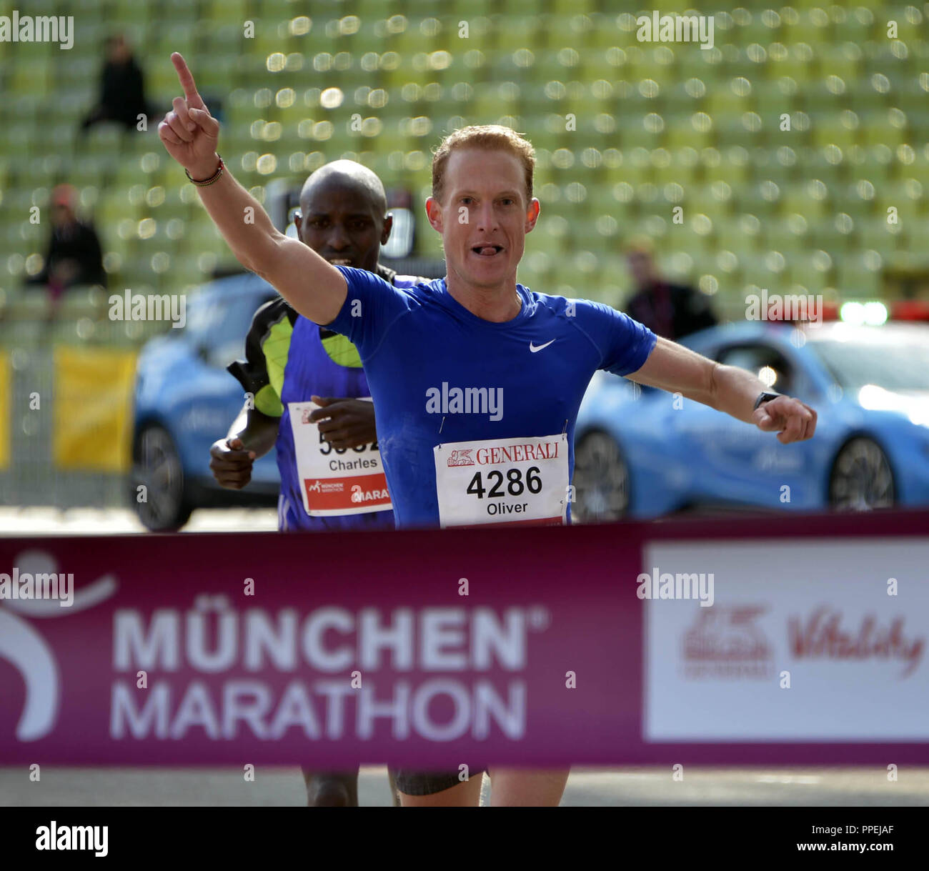 Oliver Herrmann, winner of the 31st Munich Marathon, at the finish line in the Olympiastadion. On the second place is the Kenyan pacemaker Charles Korir. - Stock Image