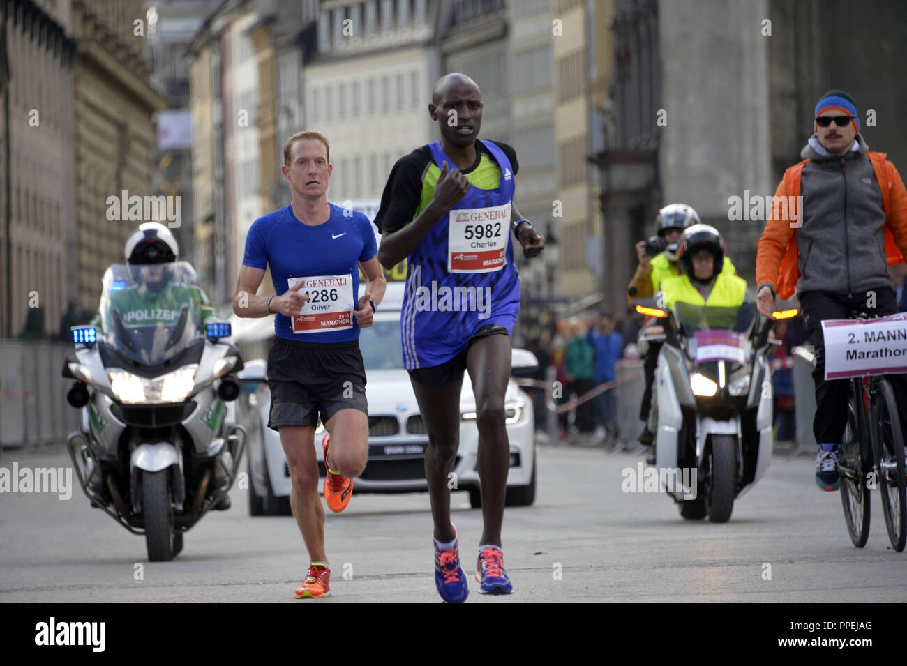 The later winner Oliver Herrmann (left) with his Kenyan pacemaker Charles Korir on the course at the 31st Munich Marathon. - Stock Image