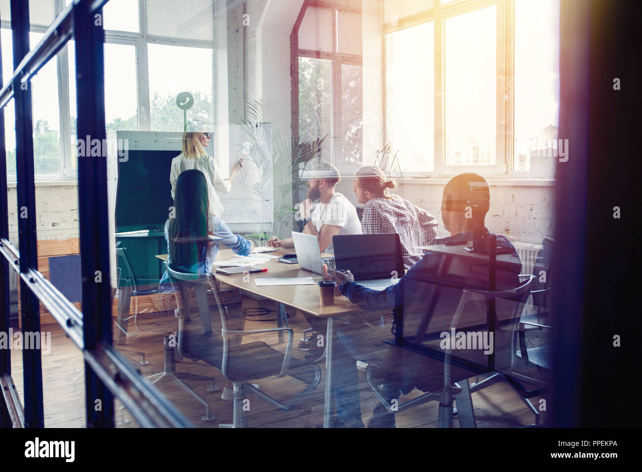 Working hard to win. Businesswoman conducting a business presentation using flipchart while working in the creative office. - Stock Image