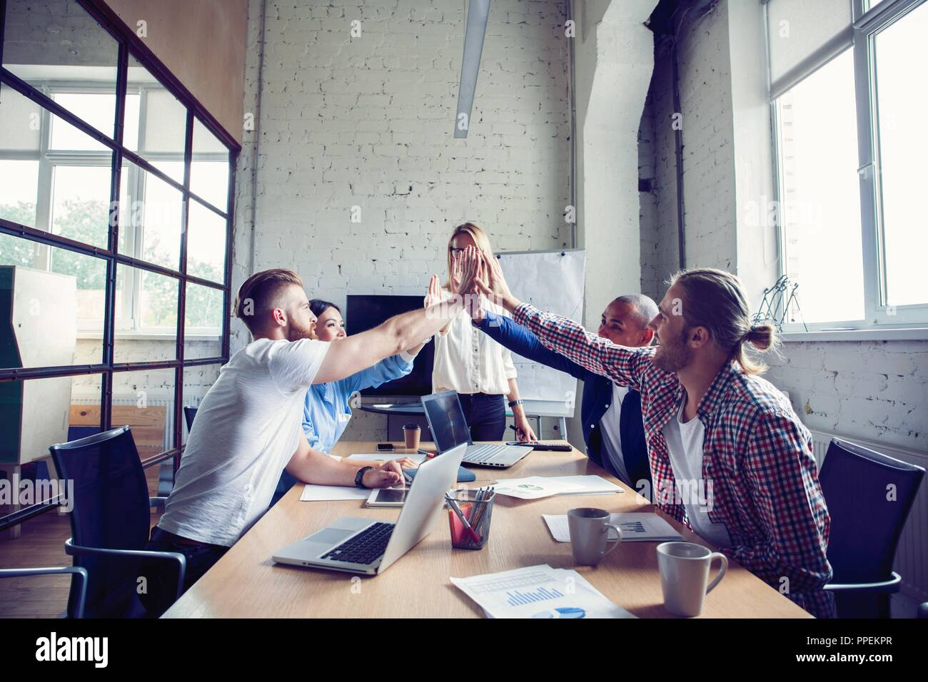 Happy successful multiracial business team giving a high fives gesture as they laugh and cheer their success. - Stock Image