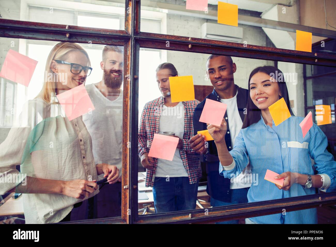 Business people meeting at office and use post it notes to share idea. Brainstorming concept. Sticky note on glass wall Stock Photo
