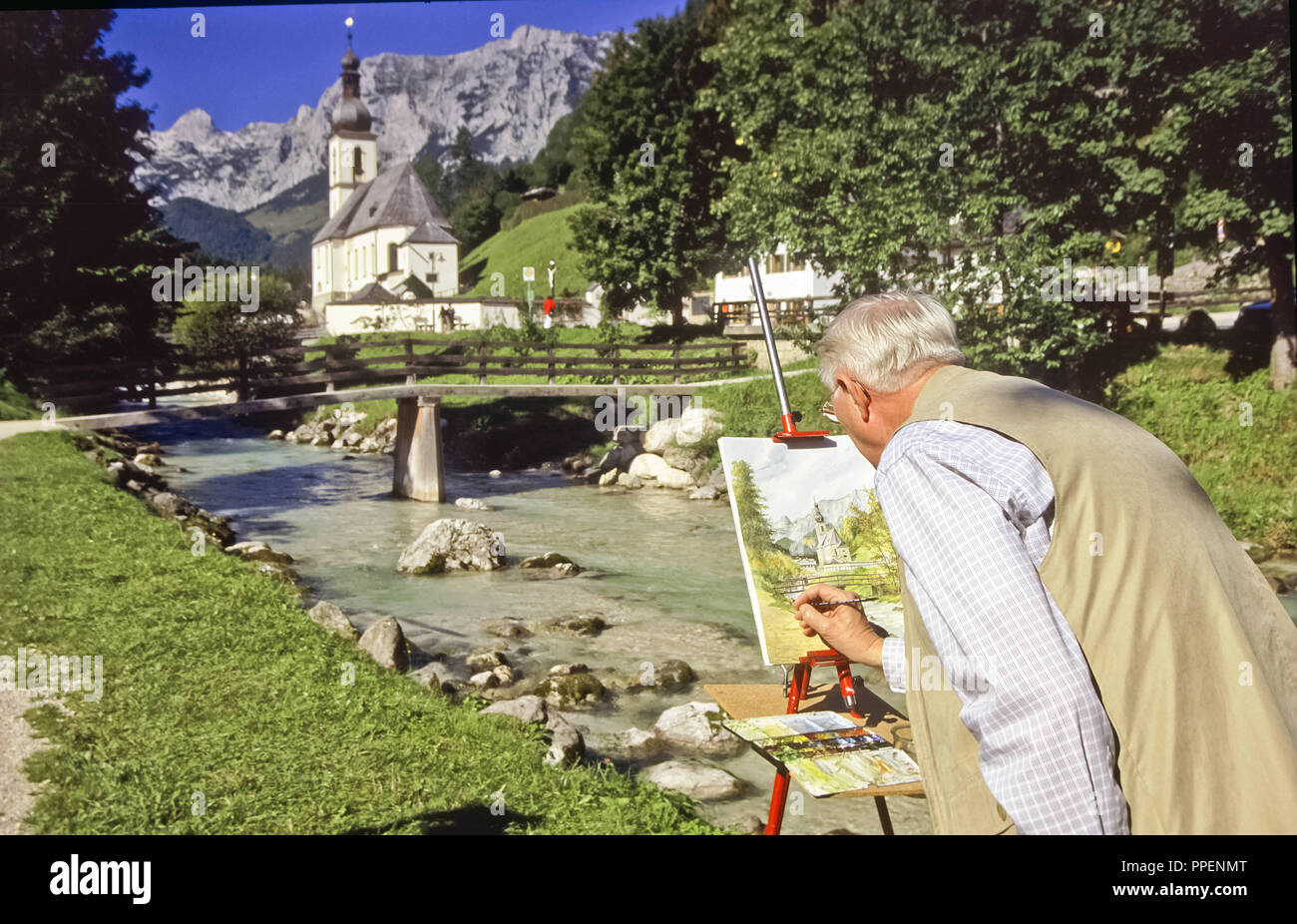 Painter before the picturesquely situated church in Ramsau - consecrated to St. Sebastian, Berchtesgaden, Upper Bavaria against the impressive backdrop of the Reiter Alpe in the Berchtesgaden Alps - Stock Image