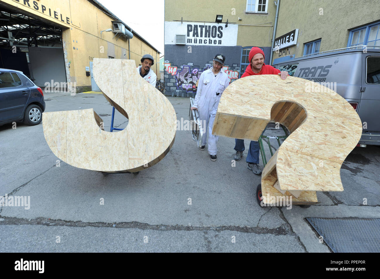 The campaign 'What's the deal' - an EU-wide art project on sustainability. In the picture the Munich-based participants Matthias Wiegele (left), Philip Metz (middle) and Tuncay Acar (right) set up in front of Hall 6 at the Dachauerstrasse their nomadic sculpture 'Die 3 Fragezeichen' (The 3 Question Marks), which later is to be converted into a skateboard ramp. - Stock Image