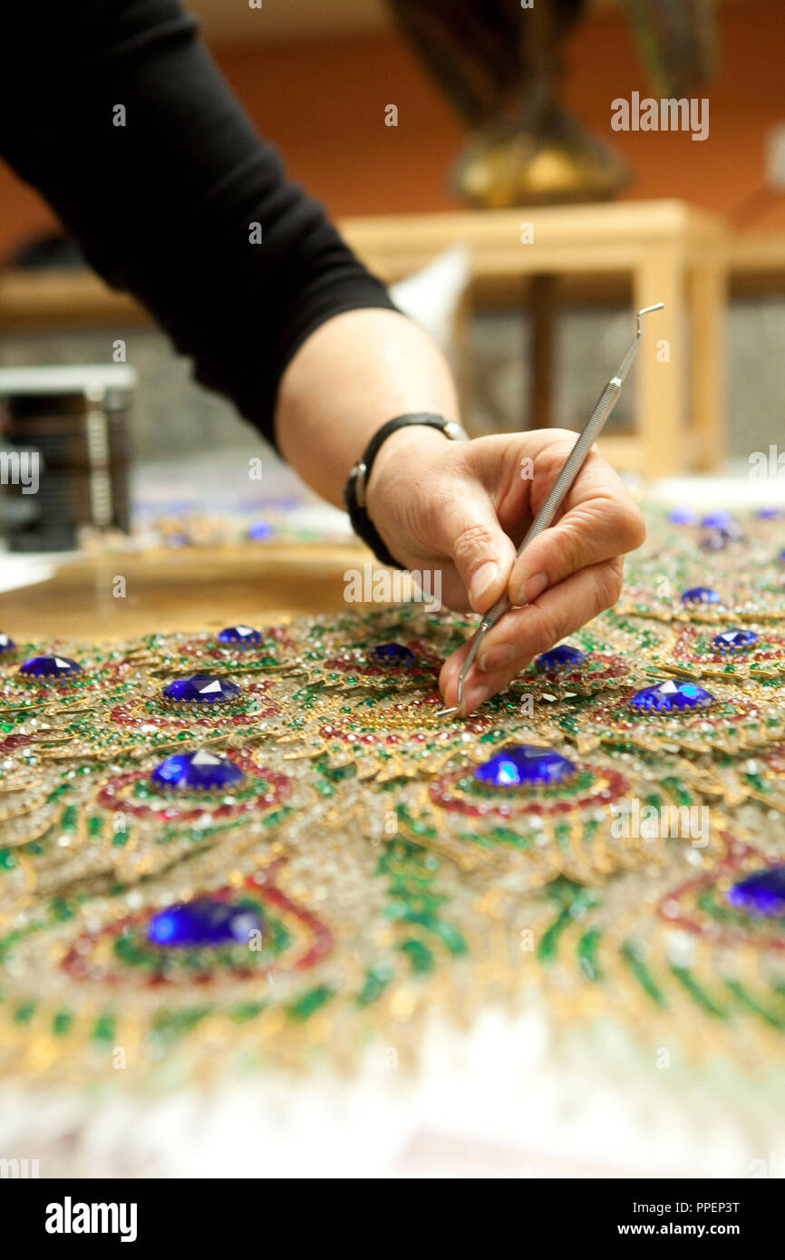 Ingrid Thon restores a peacock's fan from Linderhof Palace. Certain stones are replaced, every piece is cleaned. Here she checks the cramps, the supports for the glass blocks. - Stock Image