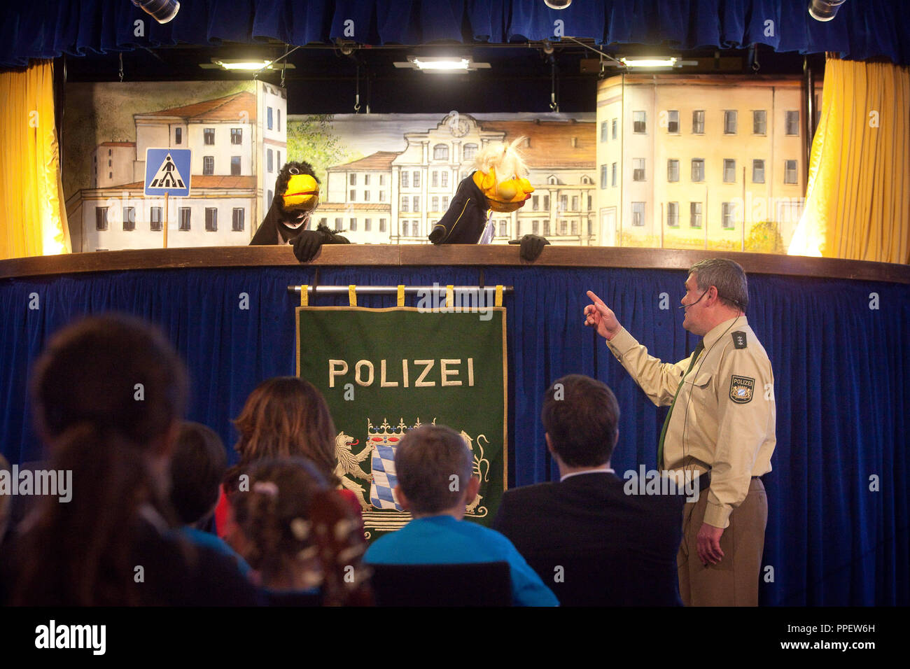 Puppetry of the police at the handover of plans of the safest ways to school to prepare the upcoming first-graders at the BMW Welt in Munich. - Stock Image