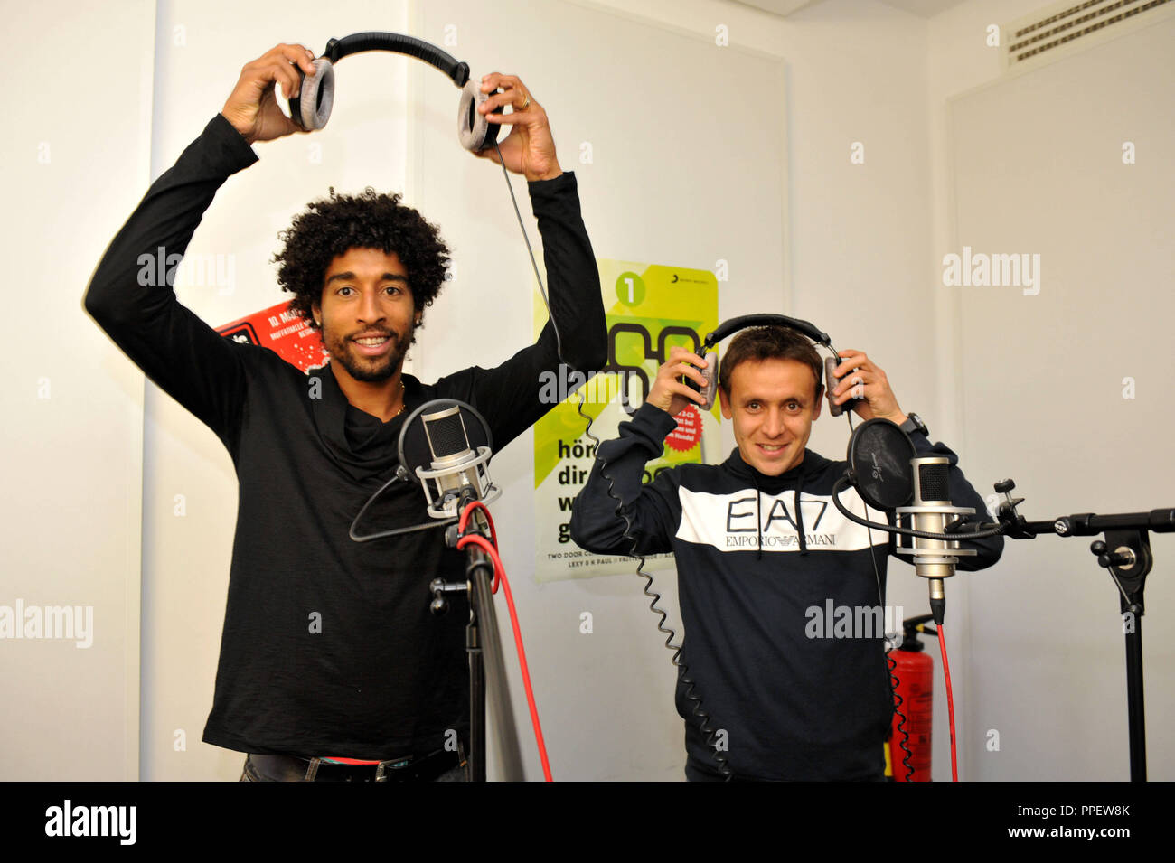 The Brazilian professional football players Dante (left) and Rafinha from Bayern Munich advertise in a broadcast of Radio egoFM the concert project 'Music for Goals', which turns against racism, xenophobia and violence in society. - Stock Image