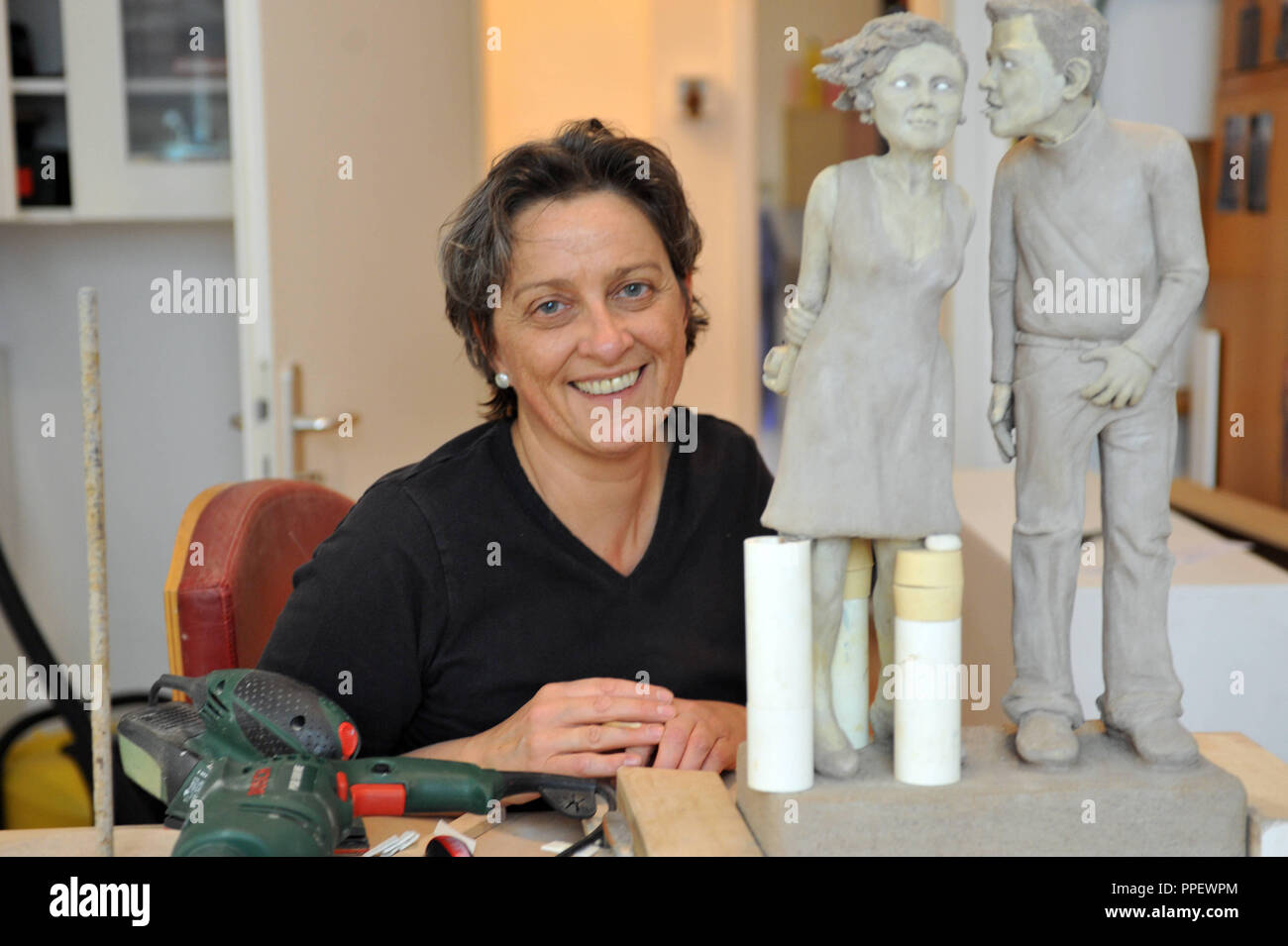 The sculptor Angela Eberhard forms small ceramic figures - people with flab, wrinkles and sympathetic ticks. - Stock Image