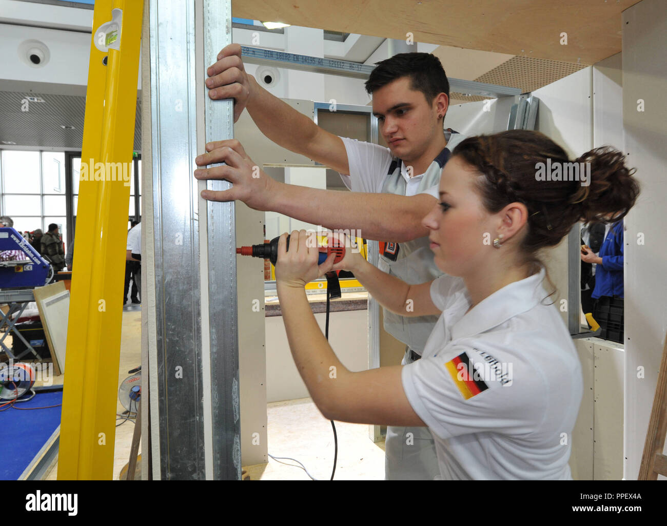 The plasterers Julia Leibold and Jonathan Stirnweiss prepare in the training camp of the German national team of the Construction Confederation at the exhibition 'Bau 2013' for the WorldSkills competition in Leipzig. - Stock Image