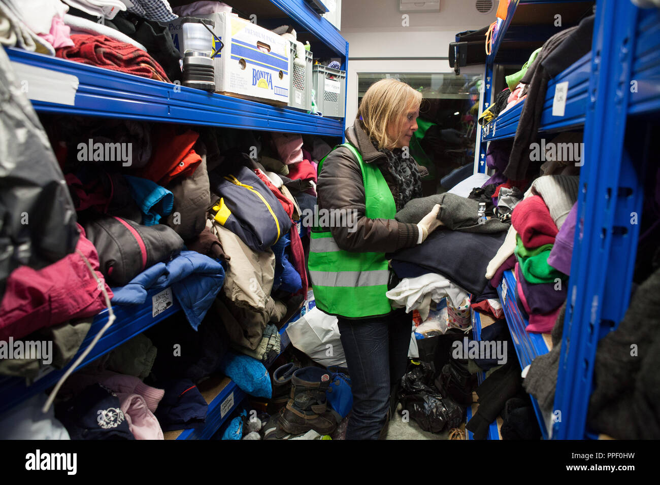 The voluntary ZOB-Angels take care of refugees stranded or waiting for their journey at the Central Bus Station (ZOB) in Munich They talk to refugees, distribute food, tea, and warm clothes. In the picture, a helper in a container with warm clothes, blankets and sleeping bags. - Stock Image