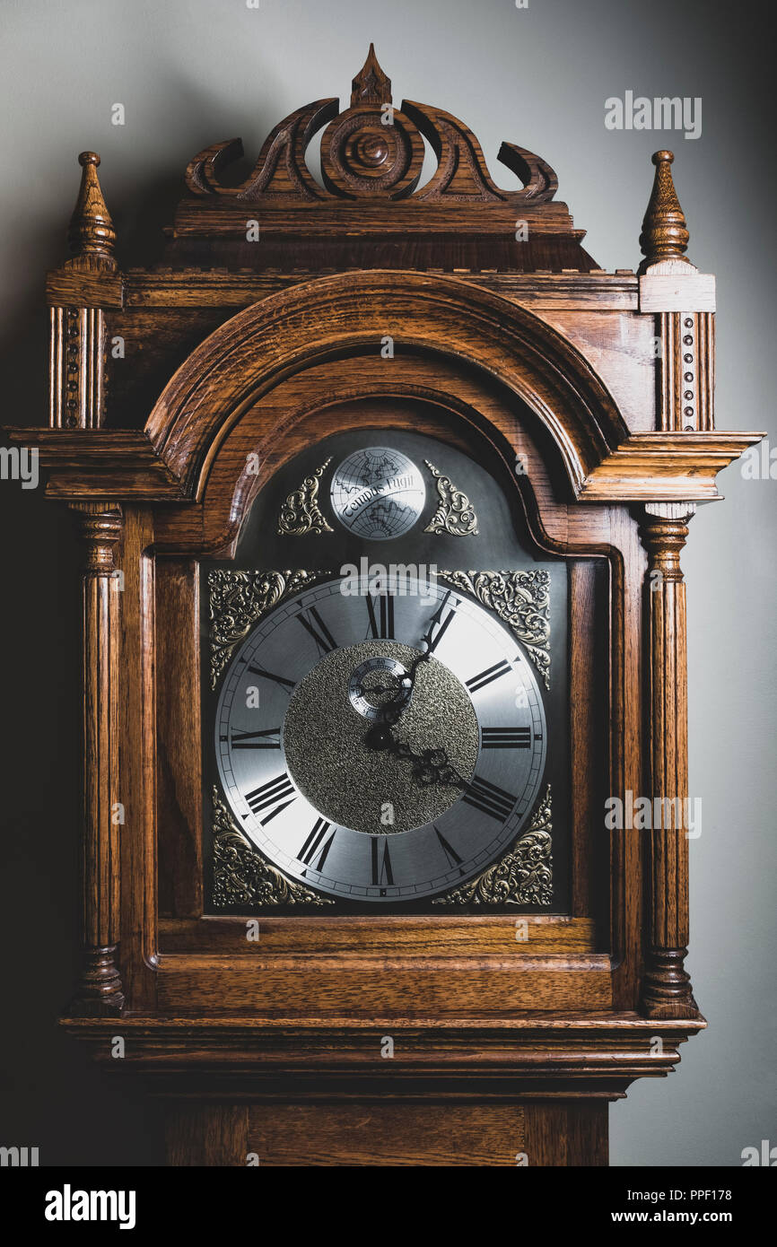 A wooden grandfather clock face. - Stock Image
