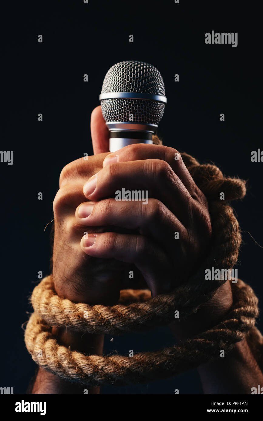 Freedom of speech, conceptual image with male person holding a microphone with hands tied in ropes, low key image - Stock Image